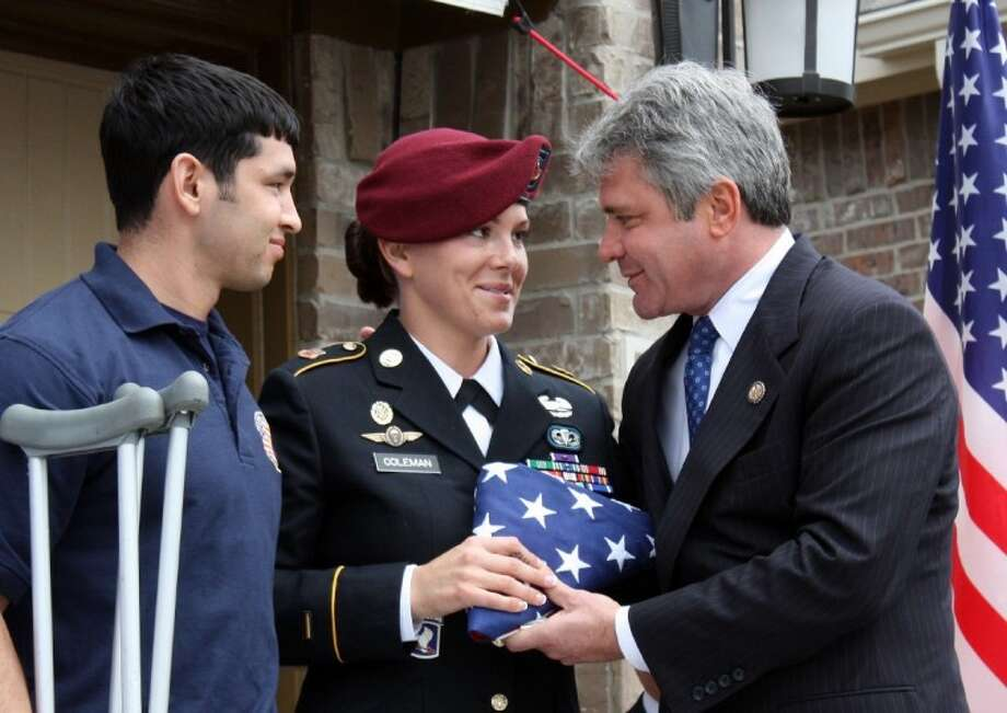 U.S. Rep Michael McCaul, right, presents Sgt. Kendra Coleman with a flag that was flown over the U.S. Capitol in her honor. With Coleman is her husband, Anthony Garza.