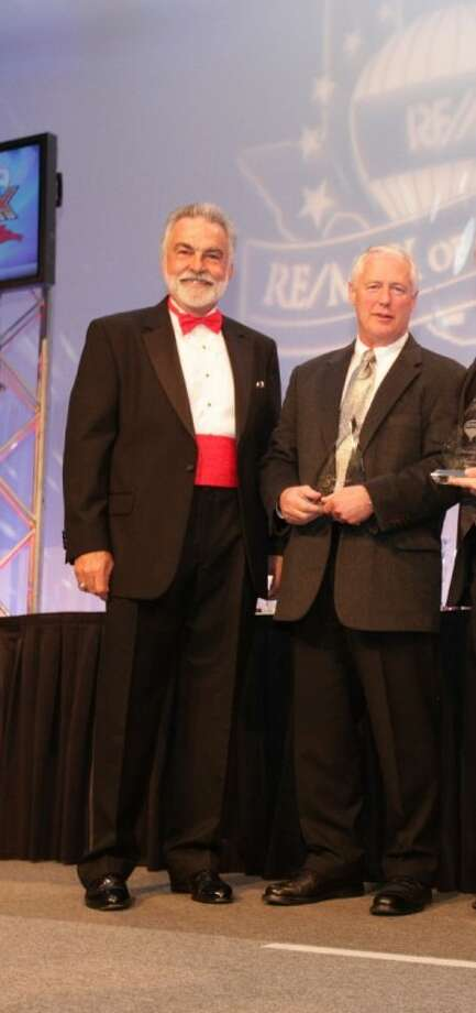 Mike Seder, right, accepts his award for top individual RE/MAX agent in Texas from Richard Filip, CEO of RE/MAX of Texas.