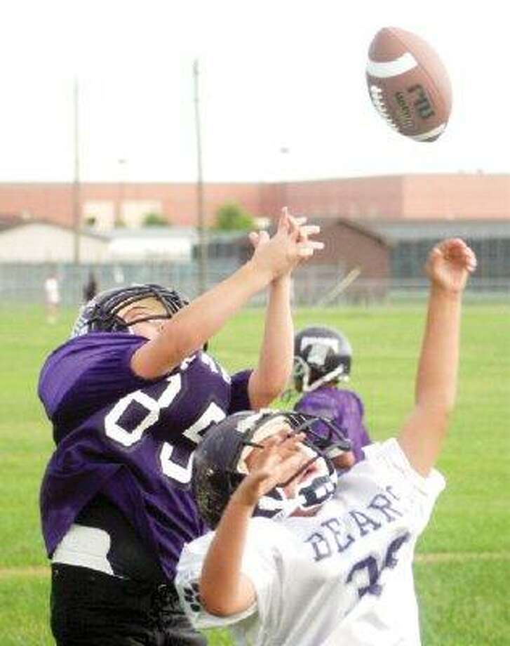 Two Pasadena Junior Bears deflect the football during a Friday night practice. The TIFI program is gearing up for another 10-week campaign.