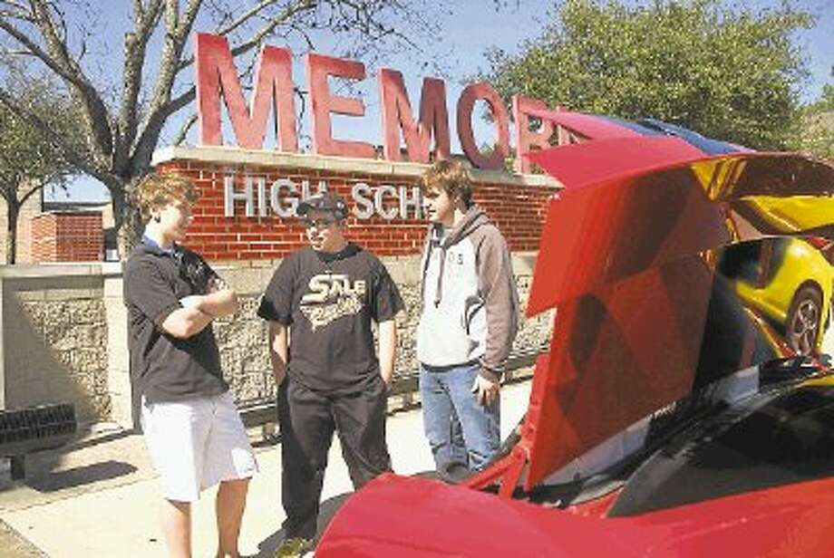 Burke Abercrombie (left), Tyler Sale and John Lohwe talk about cars Saturday. They're behind Abercrombie's 2006 Ford Mustang, with another car reflected off the raised trunk. Photo: Rusty Graham / @WireImgId=2615757