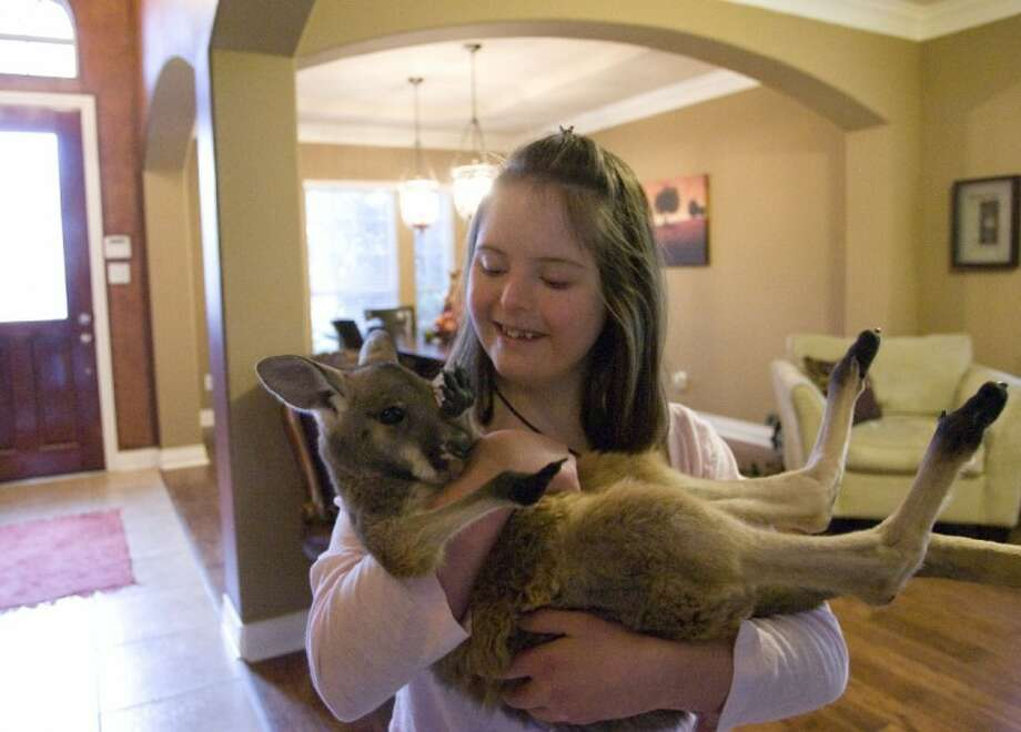Kayla Dreis, 16, holds Mike, a 6-month old baby red kangaroo, at the Dreis family's home in Spring.