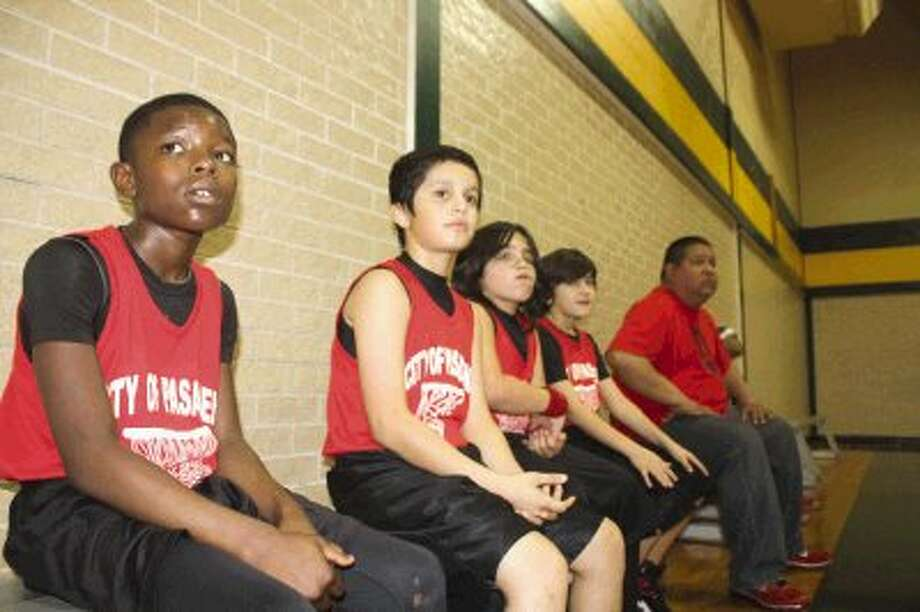 Members of the 9 and 10-year-old Mustangs youth basketball team watch the fourth-period action unfold during their opening playoff game last Saturday at Park View Intermediate. The Mustangs won this game 31-4, but saw their season end later in the day, following a 35-27 loss to the Knicks in the quarterfinals. Photo: Photo By Robert Avery