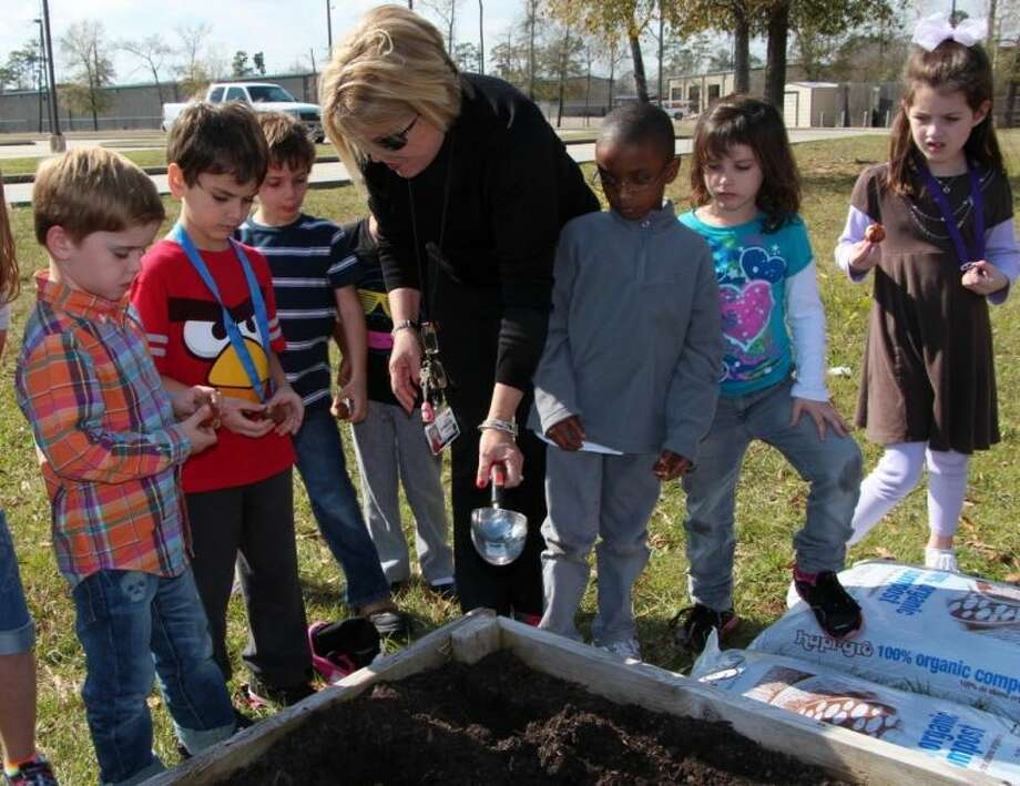 Peggy Clarey, Maplebrook Elementary kindergarten teacher discusses how to plant a bulb with a few of her students.