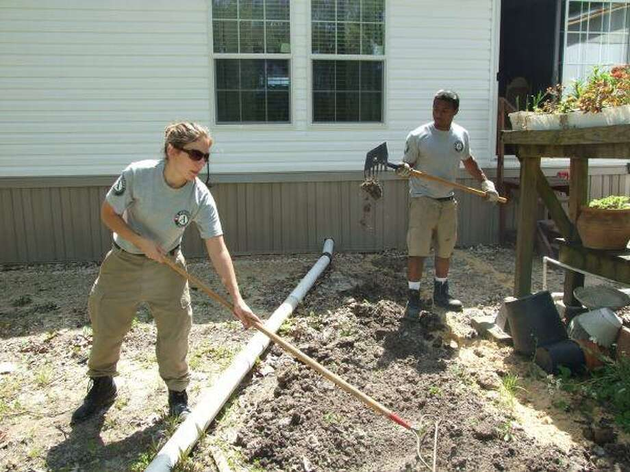 AmeriCorps volunteers Sara Millhouse, left and Terrence Foushee covered up a water line that had recently been installed for a Dayton family affected by Hurricane Ike. Foushee said that the dirt was almost as hard as concrete.