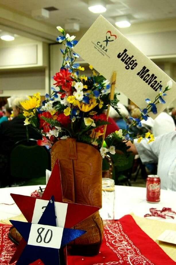 "Cowboy boots with flowers made up the centerpieces at the ""Boots and Bandanas"" banquet held Saturday evening, Feb. 23, that raised over $20,000 for CASA. Photo: CASEY STINNETT"