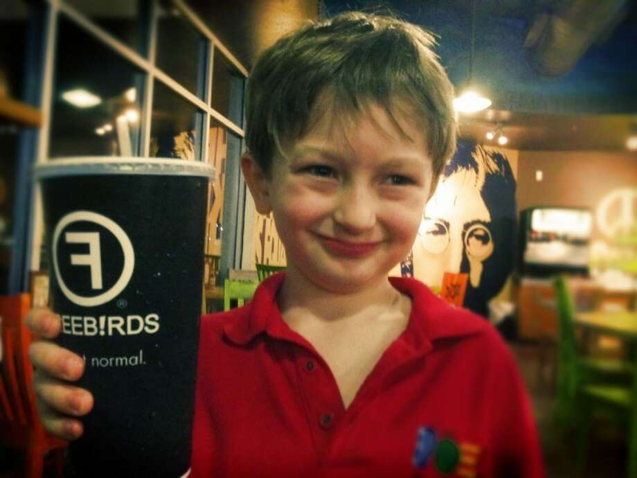 Tucker Wells, 8, at Freebirds in Sheperd Plaza. Notice the John Lennon mural in the background.