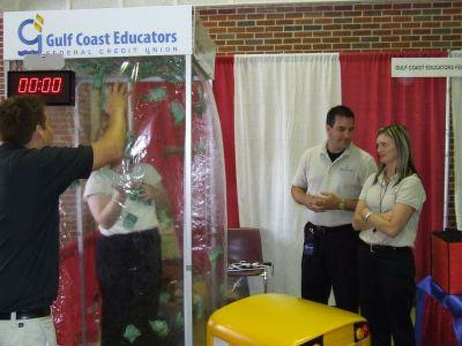 Community members and new teachers in the Deer Park Independent School District attended the Deer Park Chamber of Commerce's 2008 Salute to Education on Tuesday at Deer Park High School North Campus. Pictured is an attendee giving a try at collecting as much money as she can at the Gulf Coast Educators Federal Credit Union booth as employees look on.