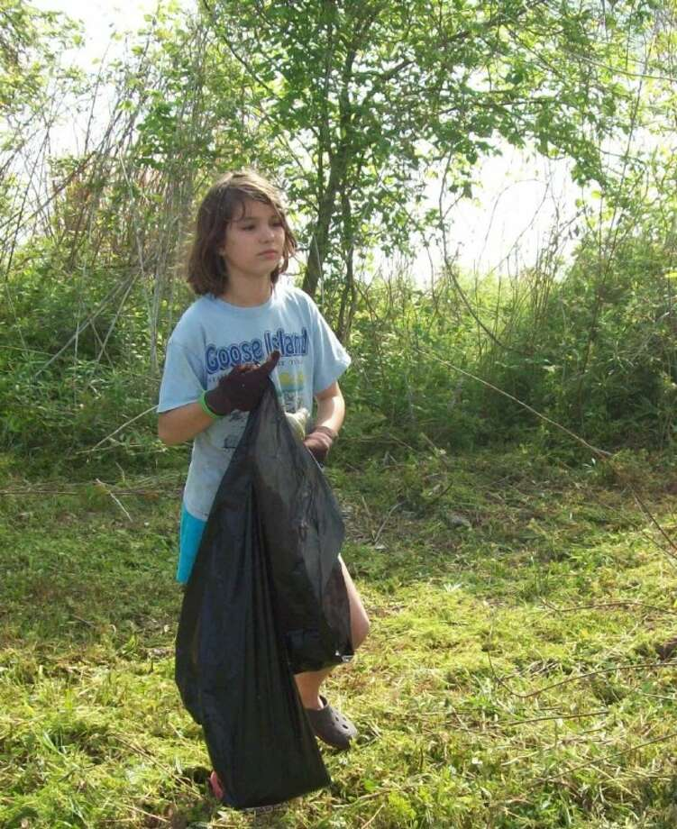Volunteer Anna Brown helps to collect trash at Lake Livingston's old 1514 Marina.