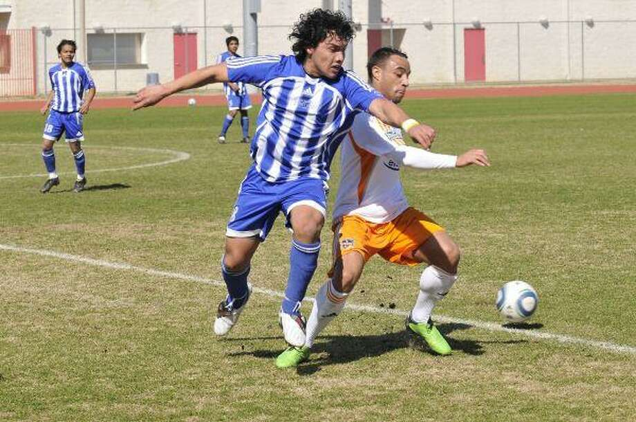 San Jacinto College sophomore Carlos Recinos attempts to steal the ball from Dynamo player Léandre Griffit.