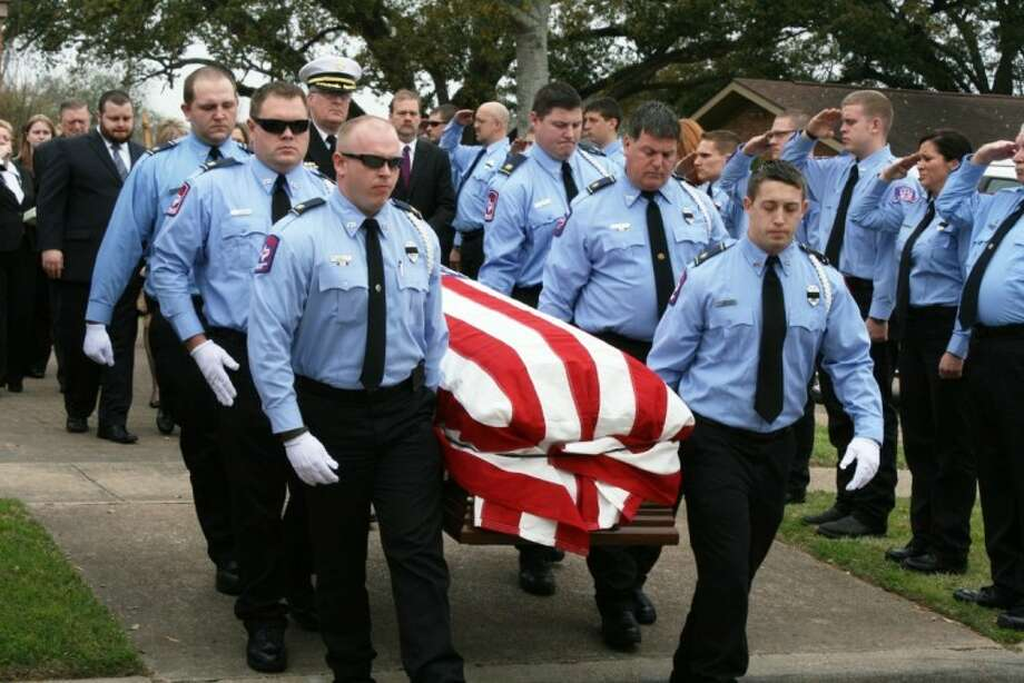 The flag-draped coffin of Larry Hajovsky is carried from Immaculate Conception Church in Liberty. Hajovsky, a Liberty firefighter, died on Friday following a brief illness. Photo: VANESA BRASHIER