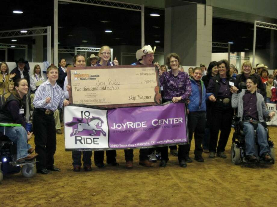Members and officials with the JoyRide Center display the $2,000 check the therapeutic horsemanship program received for winning this year's Top Hands Show.