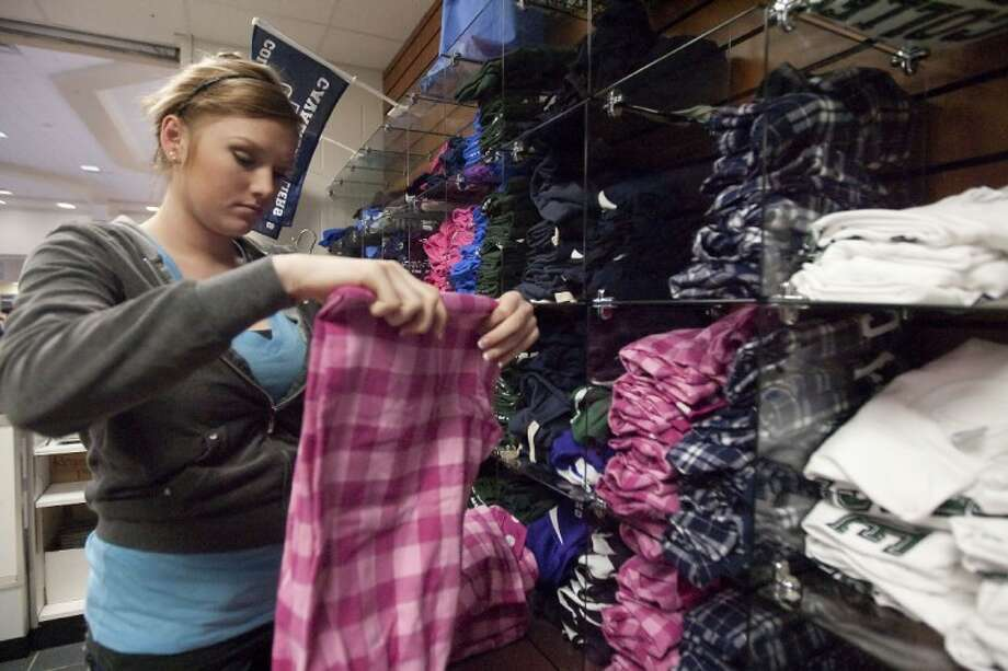 Store Manager McCall Titterington stocks the shelves with clothes at the Cavalier Express at College Park High School Monday. The Cavalier Express earned its second gold-level certification from International DECA, making it the only school in Texas to do so this year.