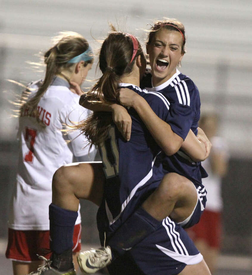 Clements' Savannah LaRicci jumps into the arms of Tory Diehl after Diehl scored on a header during the Lady Rangers' 4-0 win Feb. 22 at Travis High School. Connor Ryder (7) and Travis were undefeated in district play entering the match.Visit www.hcnpics.com for more photos. Photo: Alan Warren/HCN