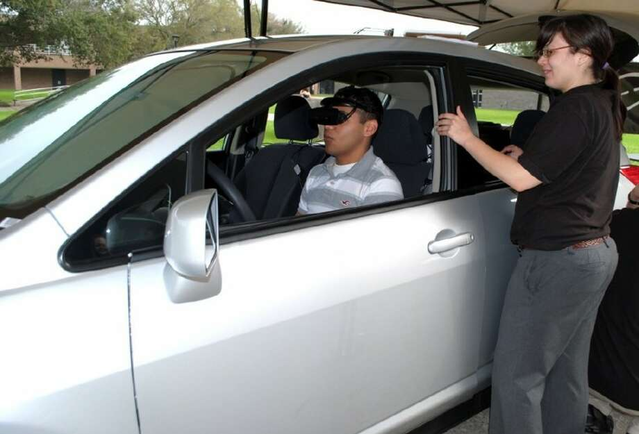 Alvin Community College student Estevan Chavez gets directions from Unite International event technician Heidi Martinez, on a driving simulation that mimics the effects of intoxication on Wednesday, February 29. Photo: ACC