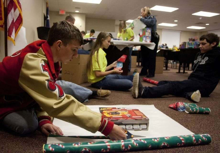 """In this Courier file photo from Dec. 2011, Trey Trott, left, and other CISD students wrap gifts as part of CISD Police Department Activities League annual """"Children in Santa's Dream program. State Sen. Robert Nichols, R-Jacksonville, filed Senate Bill 665 last week to protect Texas public schools' ability to use traditional holiday greetings such as """"Merry Christmas"""" and """"Happy Hanukkah"""" on school grounds."""