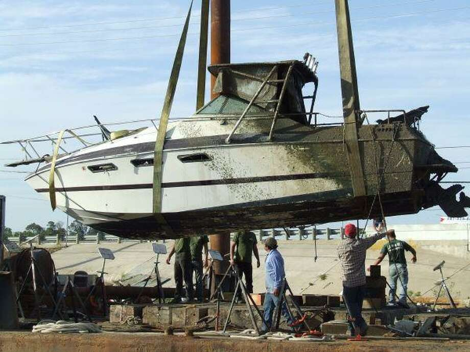 """The """"Pappagallo"""" is lowered to a barge which will move her to a lot with other boats that have been plucked from the muck."""