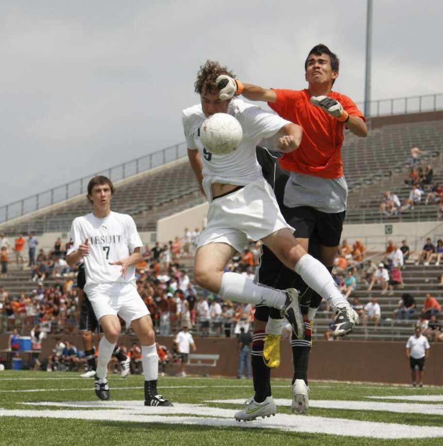 Strake senior Blake DeSpain and the Dobie goaltender go airborne and get tangled up after a shot during the Region III championship game Saturday at Galena Park ISD Stadium. The Crusaders will begin play at 4 p.m. Friday against Southlake Carroll in the 5A state semifinals in Georgetown.