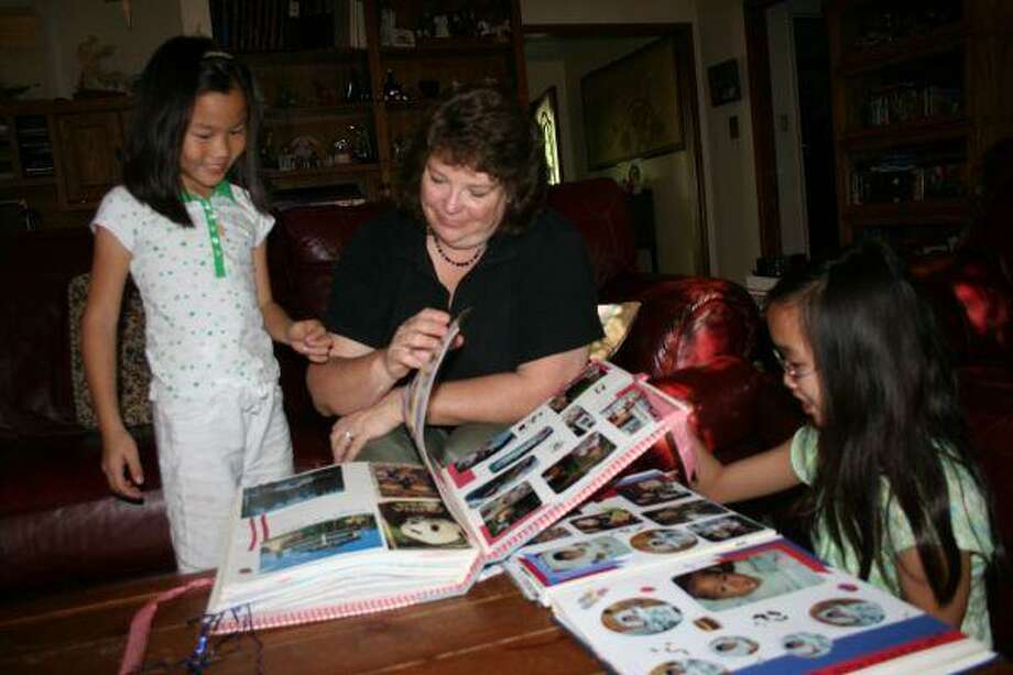 Debbie Betts and her two daughters Danielle and Christy flip through old family photo albums. Debbie and her husband Corey adopted thier daughters from China when they were only months old.