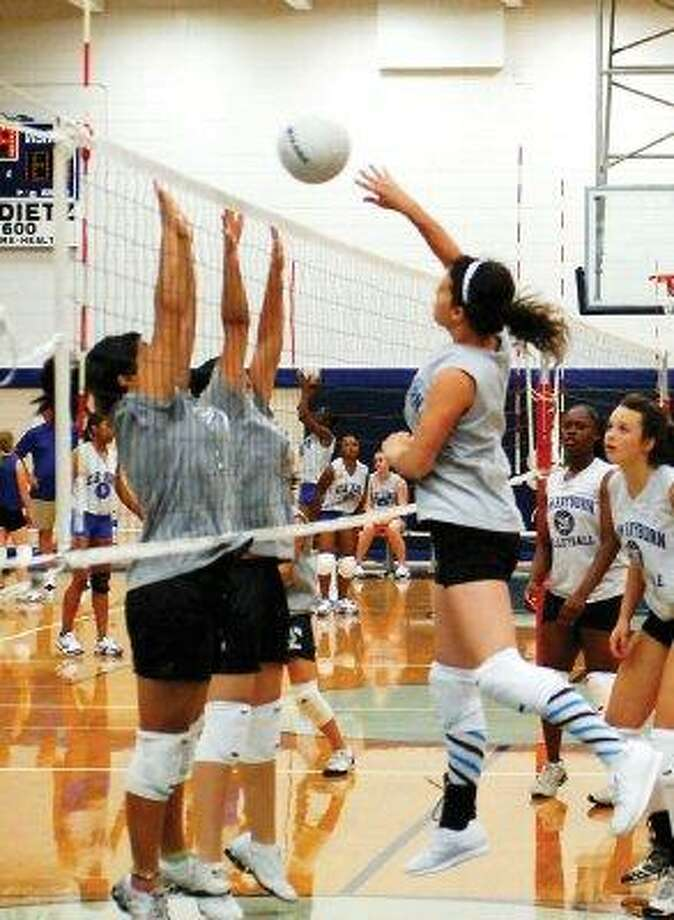 A Sam Rayburn varsity player outwits the defense at the net by dropping the ball over their outstretched arms during a Friday morning scrimmage at the school. / @WireImgId=371602