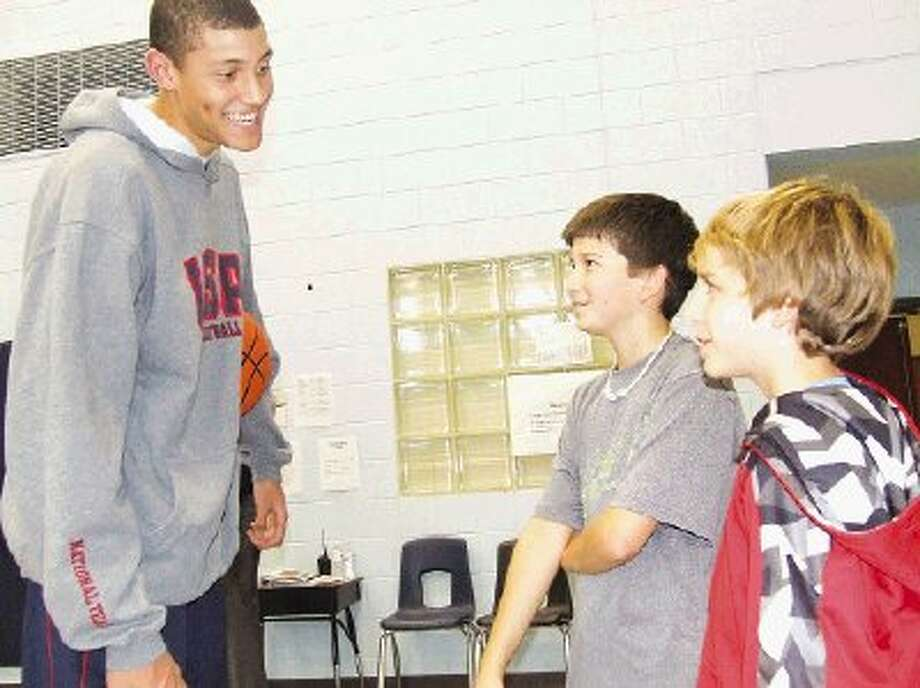 Justin Jackson, a 16-year-old USA Basketball player, talks to Northpointe Intermediate students David Forsyth, 6th grader, and Jack Worrell, 5th grader, about their favorite basketball teams.
