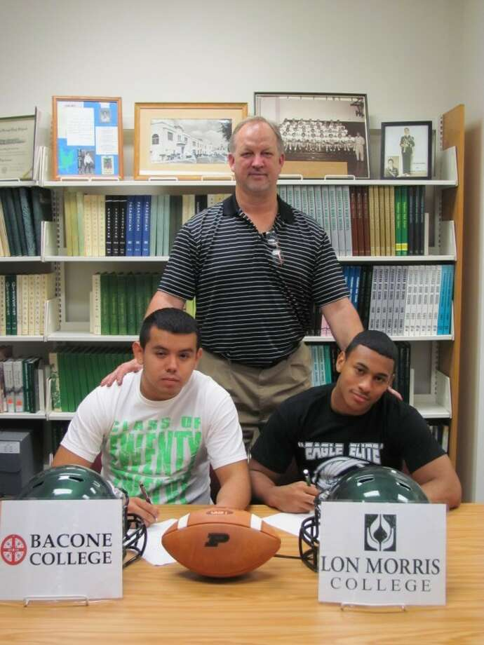 Pasadena High's Armando Lemus, left, and Julian Nance signed letters of intent to play college football beginning this fall. Lemus signed with Bacone College. Nane inked with Lon Morris Junior College. Head coach Jeff Ganske joined the pair at the signing. Photo: COURTESY PHOTO