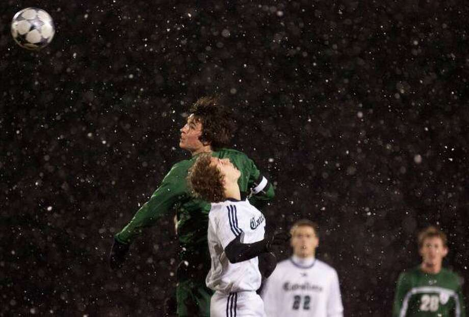 The Woodlands' Conner Cahill eyes the ball as he leaps into the air alongside College Parks' Philip Piper during a Feb. 23 game amidst a light snowfall at College Park High School. The Highlanders won 2-1 to improve to 6-0 in District 14-5A play. / The Courier