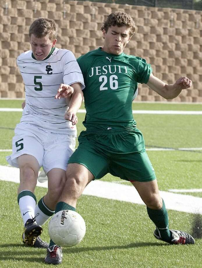 Strake Jesuit midfielder Phil Reid (26) battles with Southlake Carroll defender Jake Brillhart (5) for the ball during the second half.