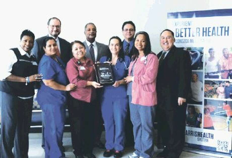 Harris Health System staff at Pediatric and Adolescent Health Center-Cypress celebrates receiving the Southwest Region Award of Excellence in Job Order Contracting-2012 Harry H. Mellon Award from representatives of the The Gordian Group.