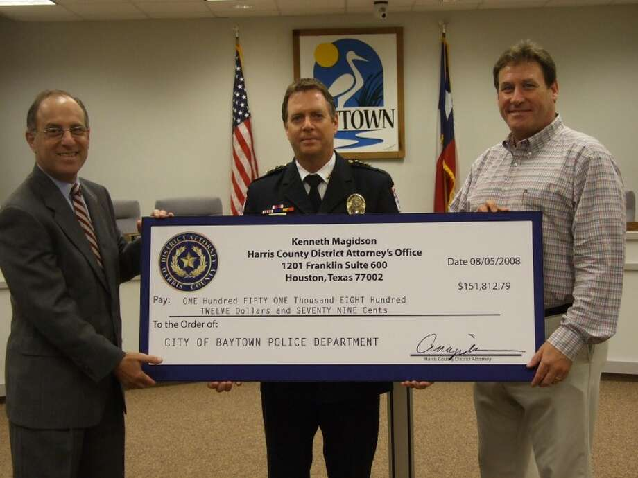 Harris County District Attorney Kenneth Magidson (left) presented the Baytown Police Department with a check for over 150,000 Wednesday to be used to help fund the department's criminal investigation system. Also pictured are (center) Baytown Chief of Police Keith Dougherty and City Manager Garry Brumback.