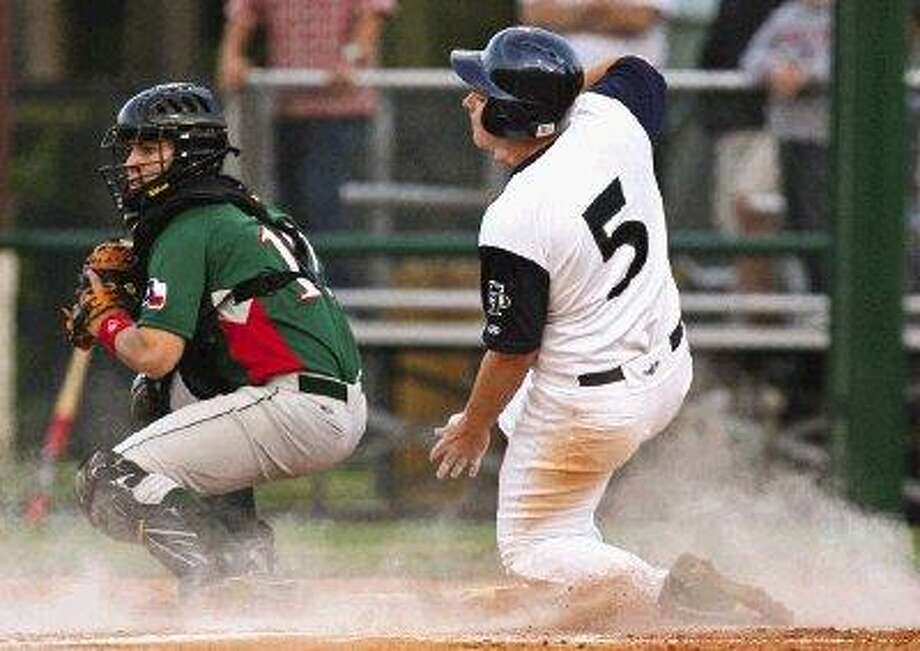 College Park's Jason East slides into home, beating the tag of The Woodlands' Daniel Homann during Friday's game at College Park High School. / The Courier