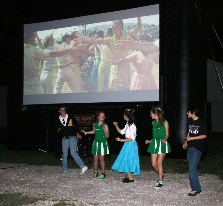 Volunteers with the Katy Visual and Performing Arts Center dance to the finale of an outdoor screening of Grease Friday night at the center in Katy.