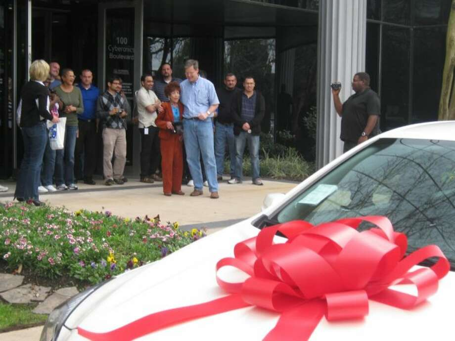 Cyberonics President Dan Moore helps Beverly McGee remain standing after she learned her 25th company anniversary gift was a new car. Photo: JEFF NEWPHER