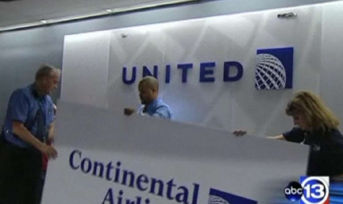 Employees at Bush Interncontinental Airport remove Continental Airline signs Friday night.