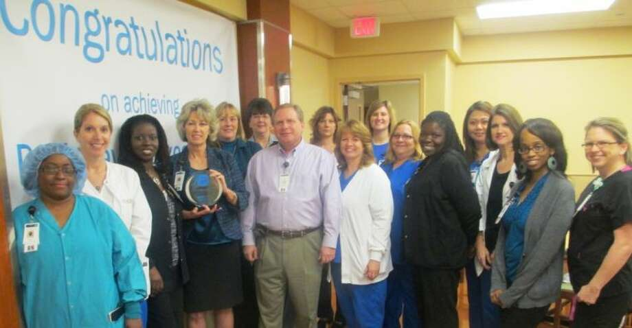 """Standing in front of a banner offering """"Congratulations on achieving Pathway to Excellence® designation, Memorial Hermann Northeast CNO Linda Stephens holds the """"Pathway to Excellence®"""" award presented to the Hospital. Joining her are members of the Nursing Team instrumental in achieving the """"Pathway"""" status."""