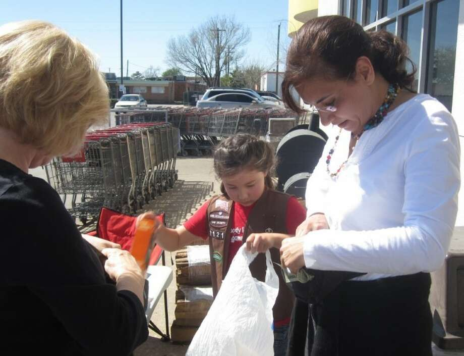 Meade takes care of the transaction with her money belt, while Brownie Rebecca Bollich, 8, a student at St. John's School, bags the merchandise Sunday outside H-E-B in Bellaire.