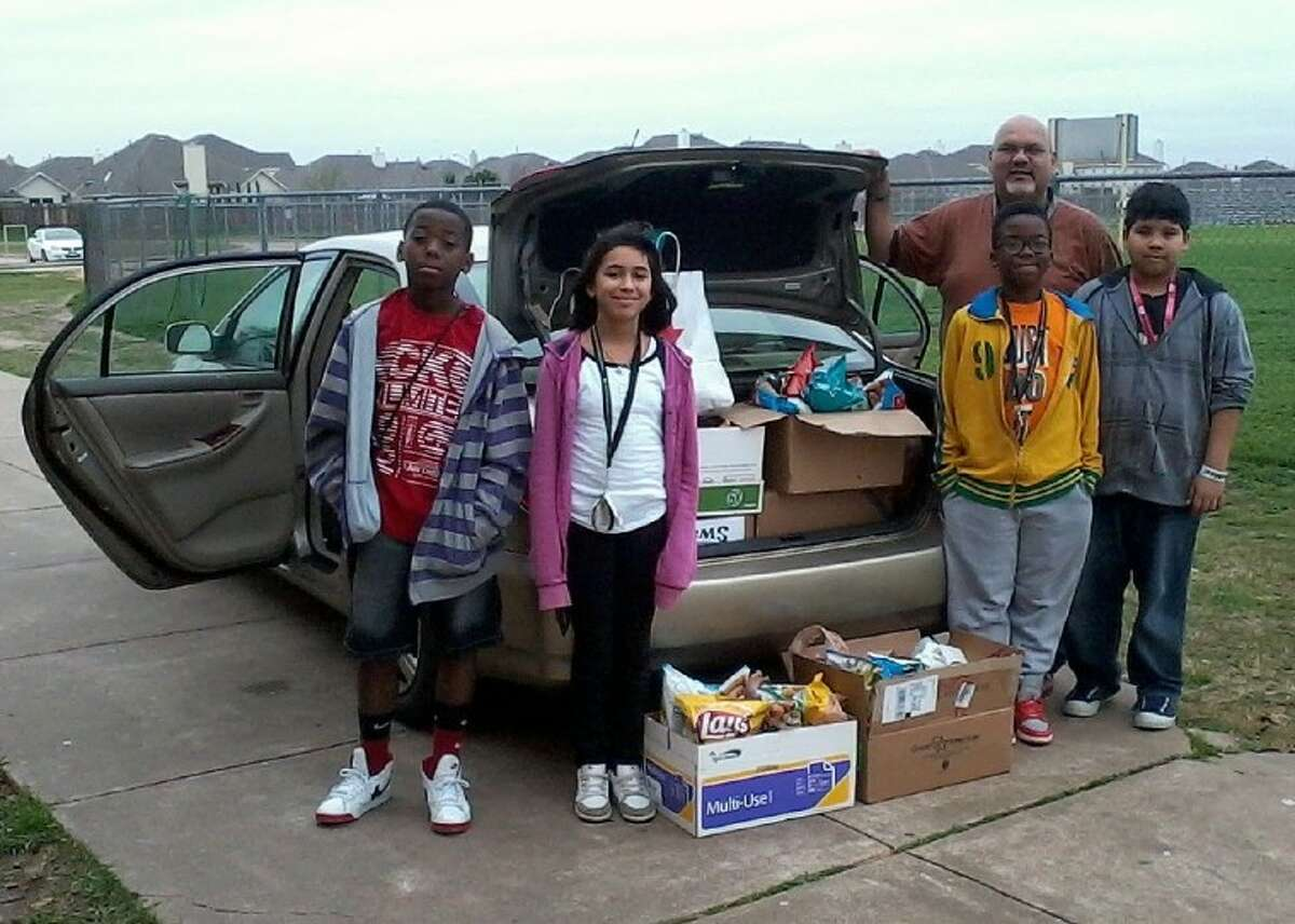 The Hodges Bend Middle School band hosted a party that asked participants to donate food items as admission. Thanks to the generous support of HBMS students, the band collected more than 400 pounds of food, which were donated to the Second Mile Mission Center in Stafford. Pictured from the left are band members Daveon Haskett, Casi Perez, Claude Minkandi and Jonathan Salazar, with Band Director Ralph Ortiz.