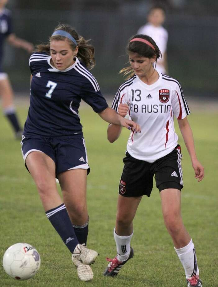 Clements' Sally Dilick moves the ball against Austin's Caroline Carvajal during a 2012 District 23-5A match. Clements leads the district by three points with three matches left, while Austin has won seven straight to close the gap. Photo: Alan Warren/HCN
