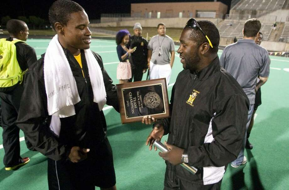 Marshall's Tyler White presents coach Lloyd Banks the championship plaque after Marshall won the 2011 District 23-5A Men's Championship at Ken Hall Stadium.