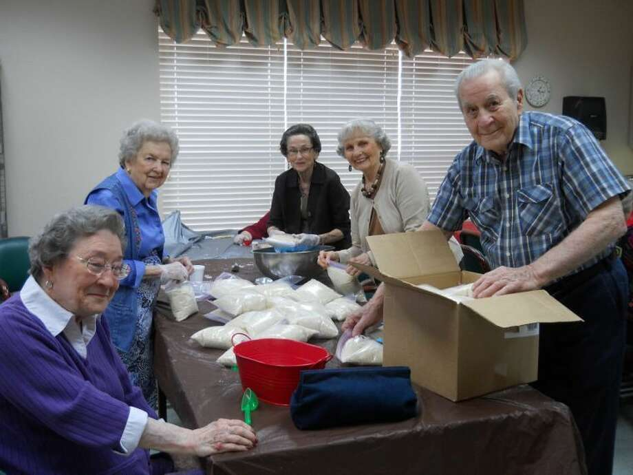 (Left to right) Mary Nell Benson, Frances Fagg, Rena Epps, Mauvirine Sorrell and Merrel Schilling bag rice for the Houston Food Bank while doing community service at Parkway Place.