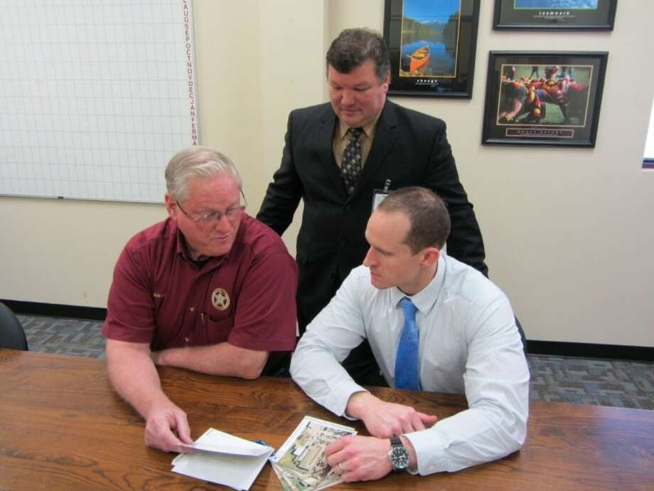 Montgomery County Pct. 5 Constable David Hill at left goes over a Rapid Responds Card set for Magnolia ISD schools with MISD Student Services Director Rob Steward (standing) and Magnolia Junior High School Assistant Principal Kent Byers. Rapid Response Cards are a tool used during school emergencies.