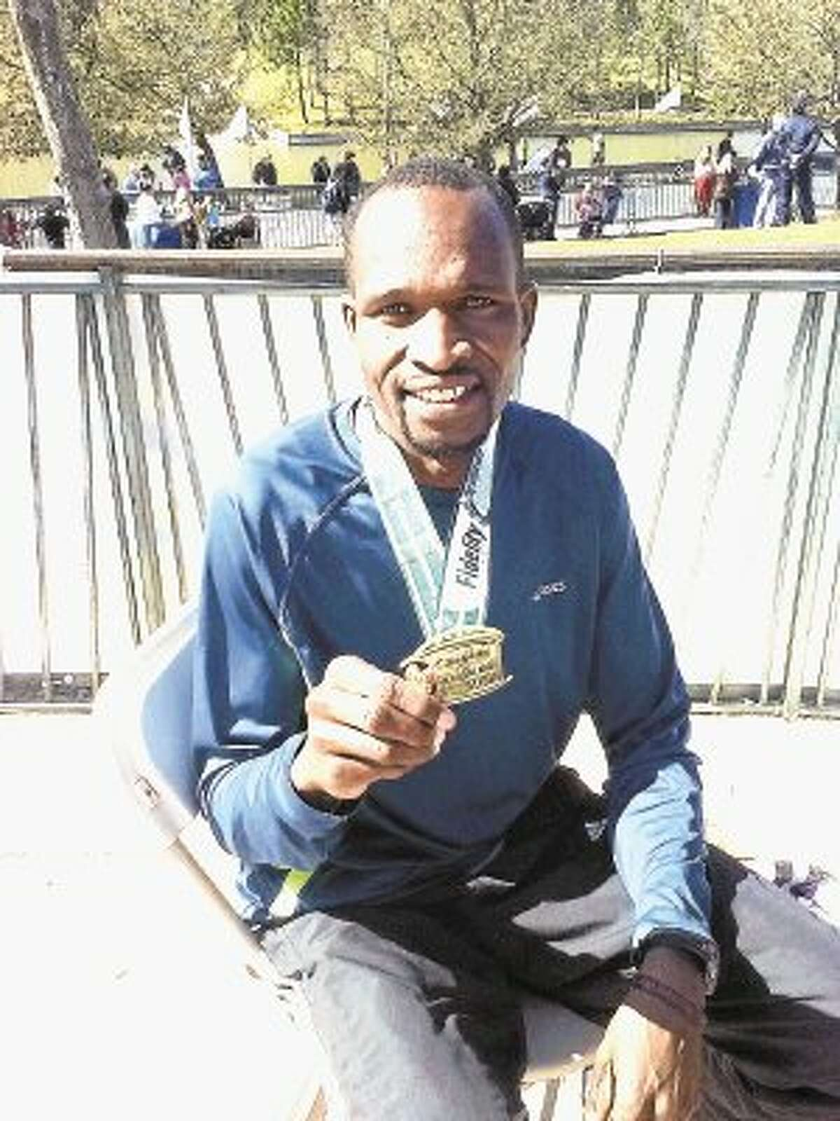 Richard Kessio of Kenya shows his medallion from winning 2013 The Woodlands Marathon.