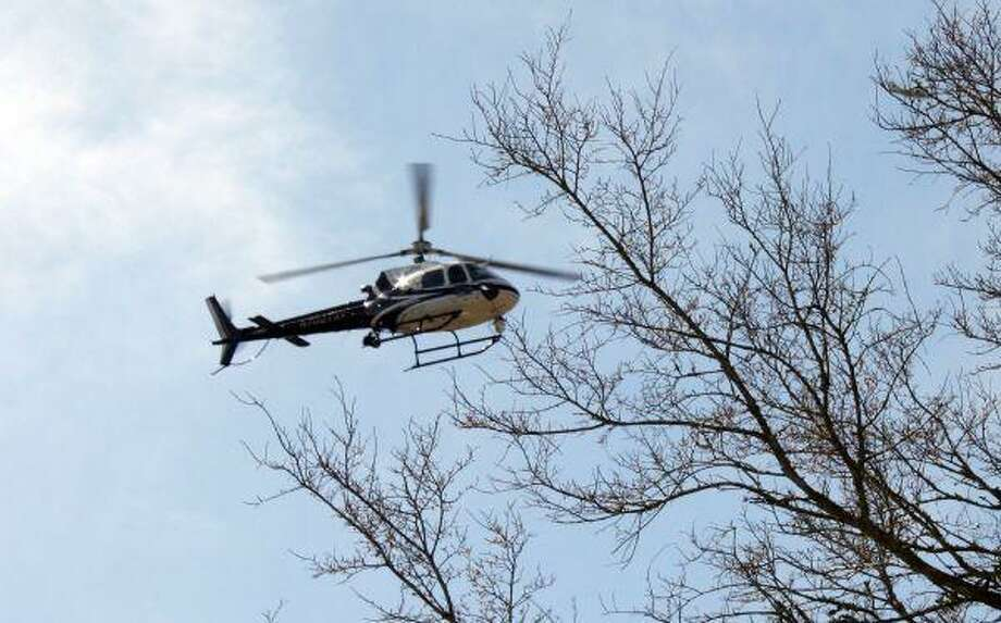 A law enforcement helicopter circles the area Thursday where the body of former FBI agent Patricia Durney was discovered off Wiggins Road.