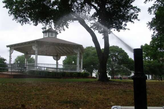 """Trees and grass at Friendswood's Stevenson Park get a """"drink"""" from sprinklers watering the area. The area is at least 10 inches behind normal rainfall levels."""