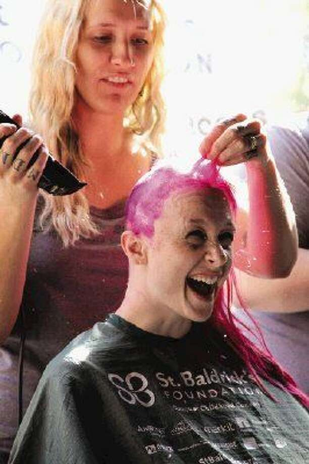 In this 2013 file photo, Tiffany Meadows reacts as her long pink hair, strand by strand, falls to the floor with each swipe of the hairstylist's clippers Sunday at the The Goose's Acre in The Woodlands.