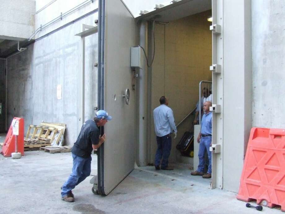 Tommy Smith, a facilities employee at the University of Texas Health Science Center at Houston, closes a massive watertight door in the Texas Medical Center facility's loading dock as part of an annual test on Saturday morning.