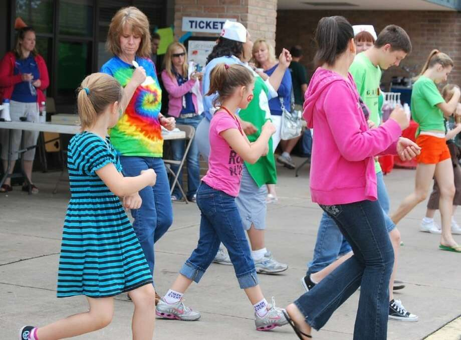Children and adults hop, twist and get low in a line dance at last year's CommUNITY Health and Safety Fair. This year's event is scheduled for March 31. Photo: STEFANIE THOMAS