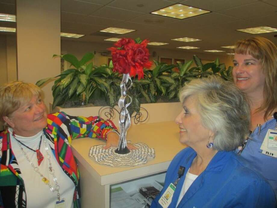 Admiring the centerpieces created for the Greater Lake Houston Go Red For Women Luncheon, from left, are Nancy Allen, Rose Marie Hartley and Missy Williams, members of the Luncheon planning committee.