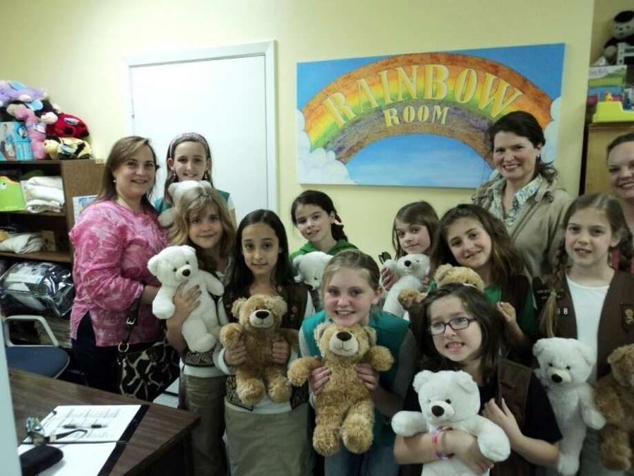 "Girl Scout Troop 11768 in The Woodlands built 12 ""Build-A-Bears"" for the Rainbow Room. Pictured are nine of the Girl Scouts and their troop leaders, Holly Griffo, Stacey Martin and Brenda Hutchinson, delivering the bears to the Rainbow Room. The Rainbow Room is located in the Child Protective Services offices in Conroe. It is a nonprofit organization that provides all new items for use by CPS caseworkers in caring for abused and neglected children in Montgomery County. For information on how to help, call 713-501-3561 or 713-301-7701."
