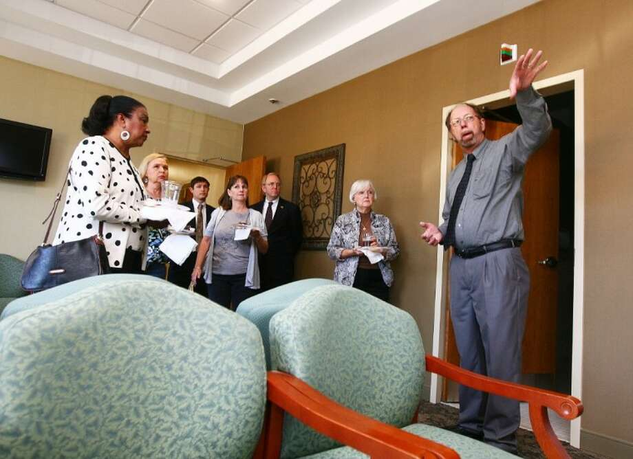 Director of Operations Don Teeler gives guests a tour of the lobby during the grand opening of Tri-County Services' Psychiatric Emergency Treatment Center May 13 in Conroe.