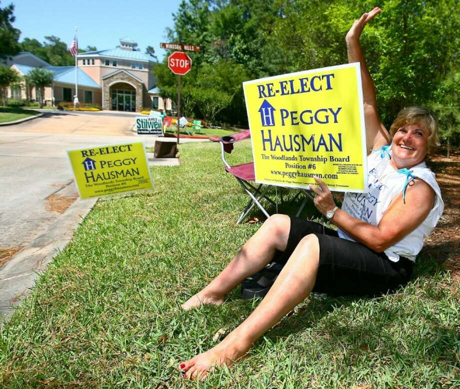 Peggy Hausman waves to cars at the entrance to the Windsor Hills neighborhood on Saturday.
